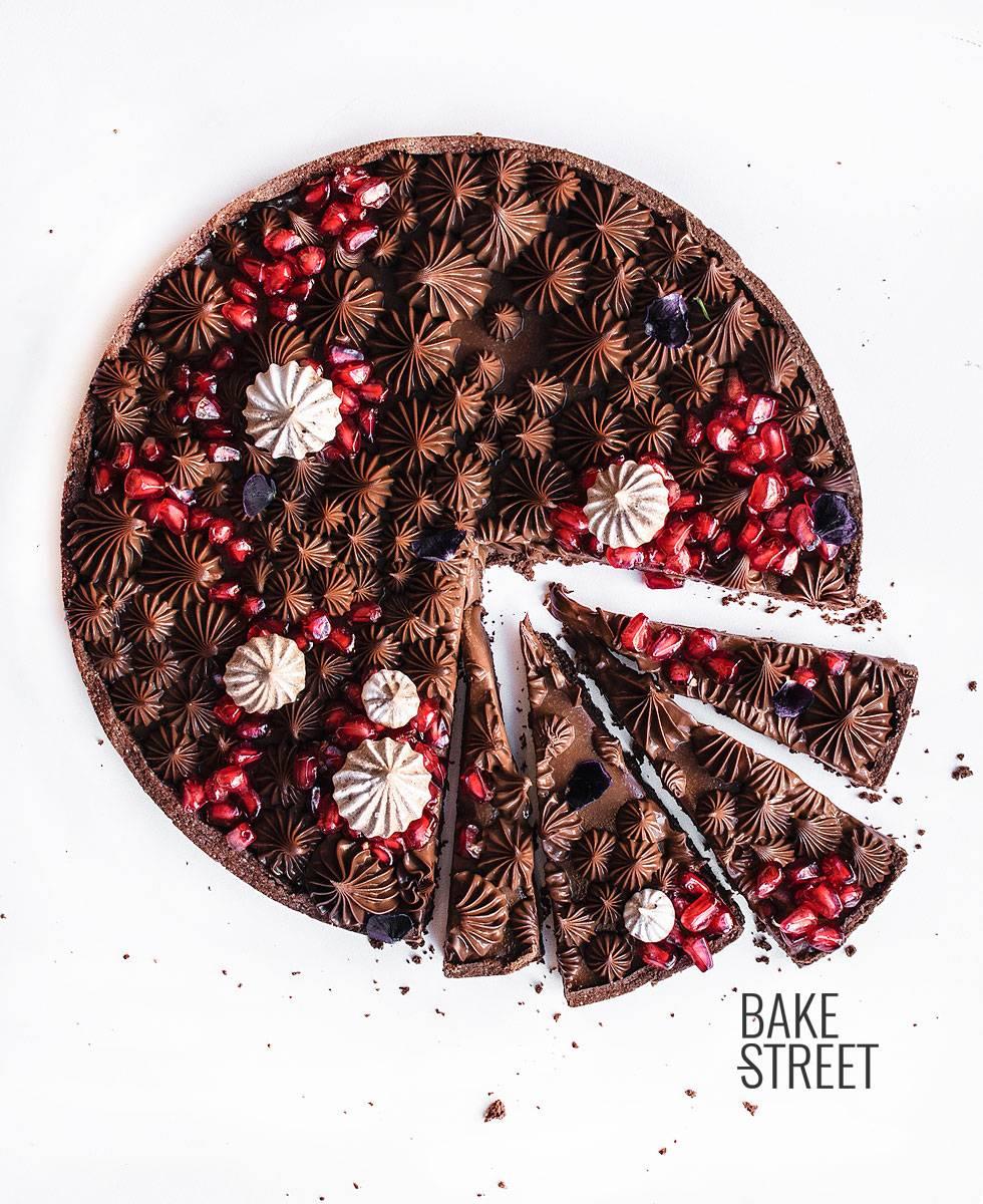 Tarta de chocolate con leche y granada, elaborada con una pâte sucrée de cacao y rellena con una ganache de chocolate con leche y canela.